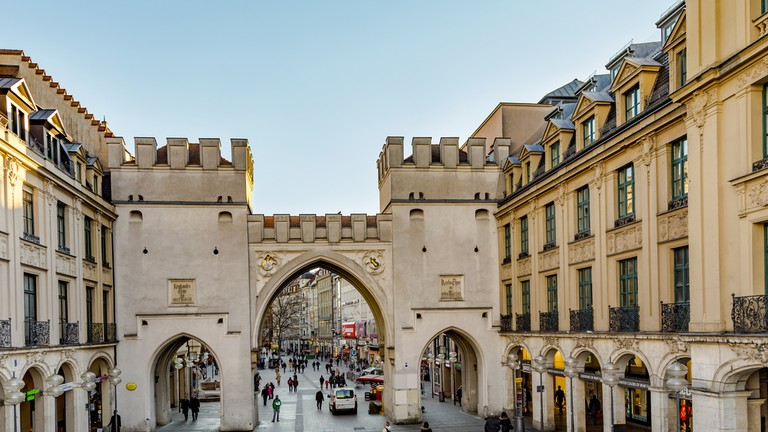 People walking along through the Karlstor gate in Munich, Germany
