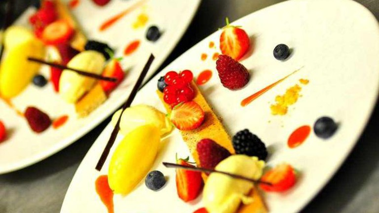 White chocolate and passion fruits mousse with red seasonal berries cake and strawberry ice cream