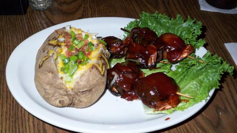 The Hoffbrau Sweetwater Shrimp Dinner: six jumbo shrimp glazed in Dr Pepper BBQ sauce, stuffed in whole jalapeño peppers and wrapped in bacon with a loaded baked potato side