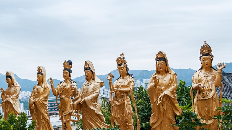 Golden Buddha statues along the stairs leading to the Ten Thousand Buddhas Monastery and landscape with green trees in the background in Hong Kong. Ho