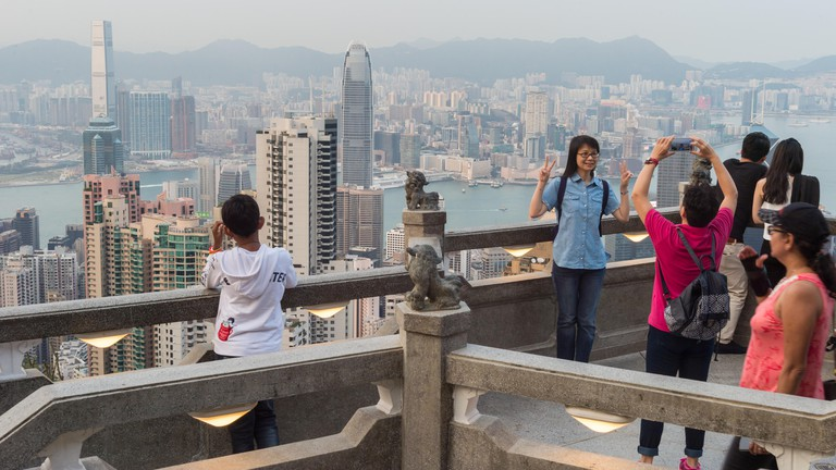 Hong Kong, China - 6 April 2015: Tourists looking at Hong Kong Skyline from Victoria Peak