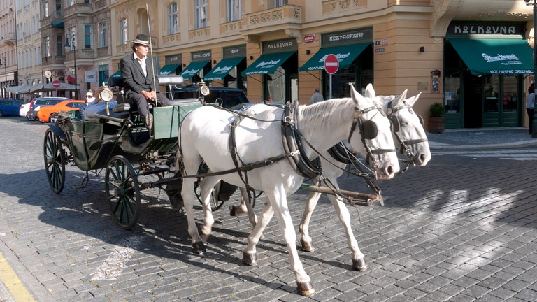 A horse carriage travels down a street in Old Town, Prague