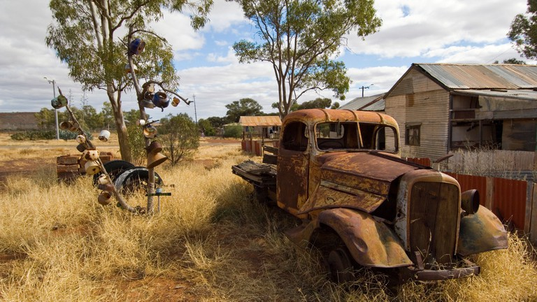 A rusted truck sits outside preserved miners' cottages in Gwalia