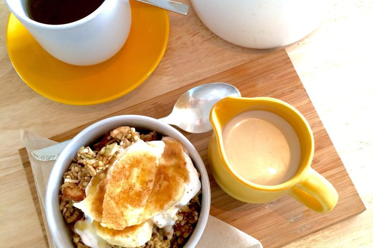 Almond granola with almond milk and banana, with a side of coconut tea