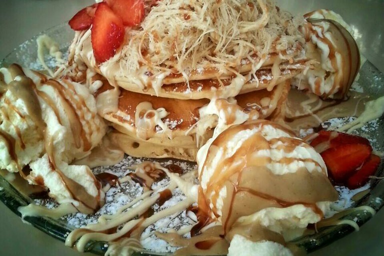 Pancakes topped with Halva, strawberries and fudge with a side of ice cream.