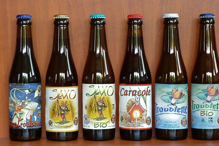 The beers of the old-fashioned Caracole Brewery, all hand labeled with various designs featuring their signature slug mascot (caracole in French)