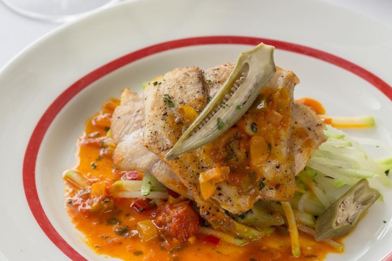 Arnaud's Gulf Fish Mitchell, pan seared and served with a bouillabaisse reduction & mirliton-pickled okra slaw