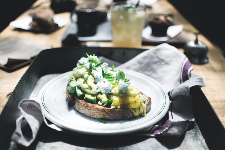 Scrambled eggs, avocado, sour cream and radish on artisan bread at HM FoodC
