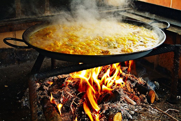 Valencian paella cooking over firewood