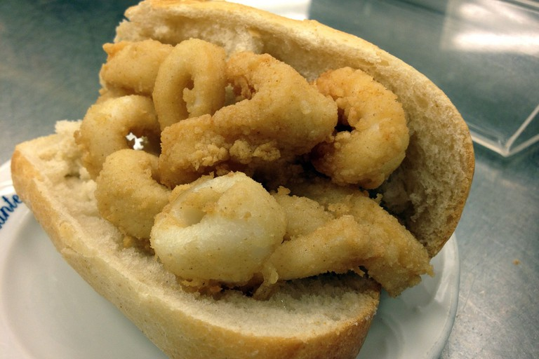 Eating a crispy calamari sandwich is a must in Madrid