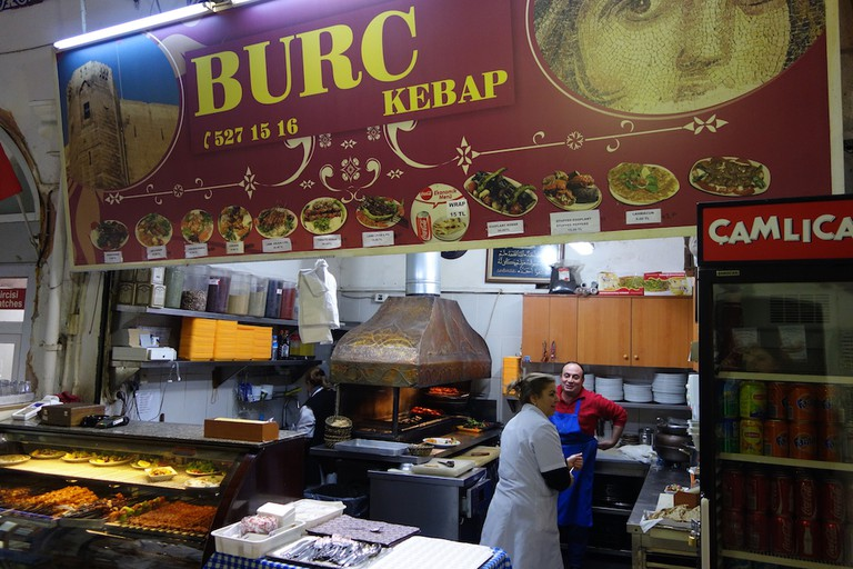 Burç Kebap cooks meat using a traditional grill