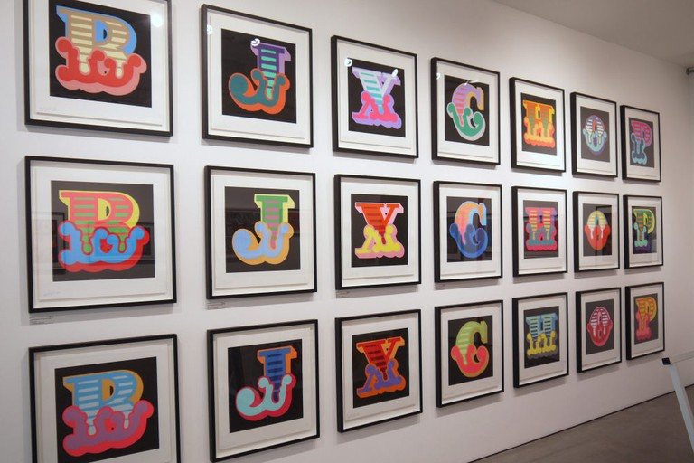 A series of Ben Eine's prints hang on the wall