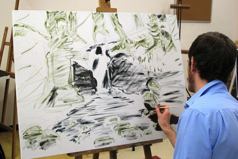 A student painting on canvas