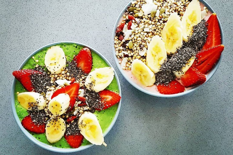 Green goodness smoothie bowl on the left, strawberries and cream on the right