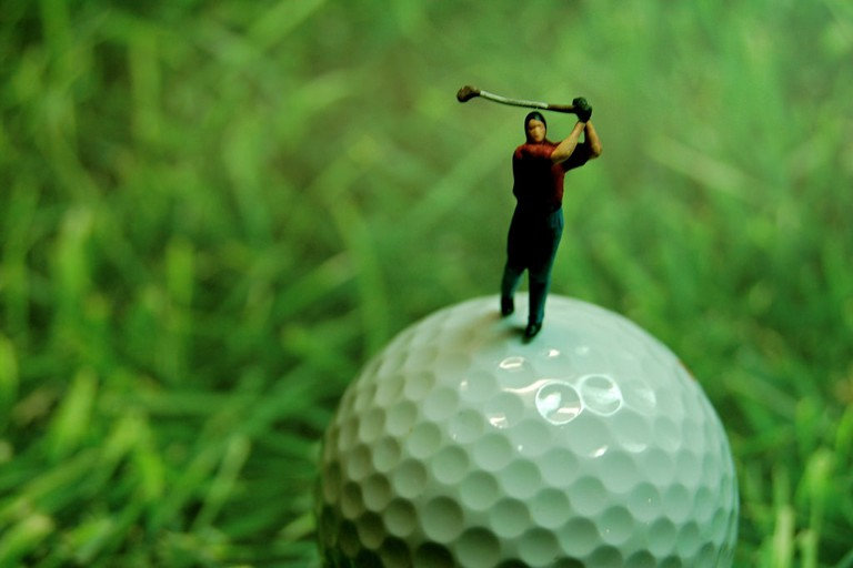 Golfing figurine stood on a golf ball