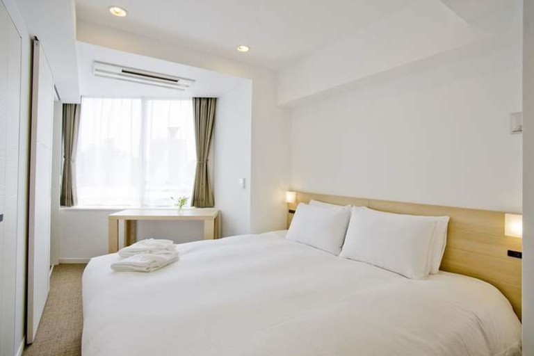 Each room at Residential Hotel B:CONTE Asakusa is equipped with a flat-screen television and a kitchenette