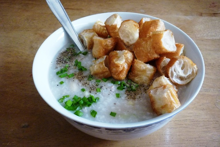 Congee with ground meat cooked with white beans, peas and fresh corn, served with Youtiao (cháo củ quả)