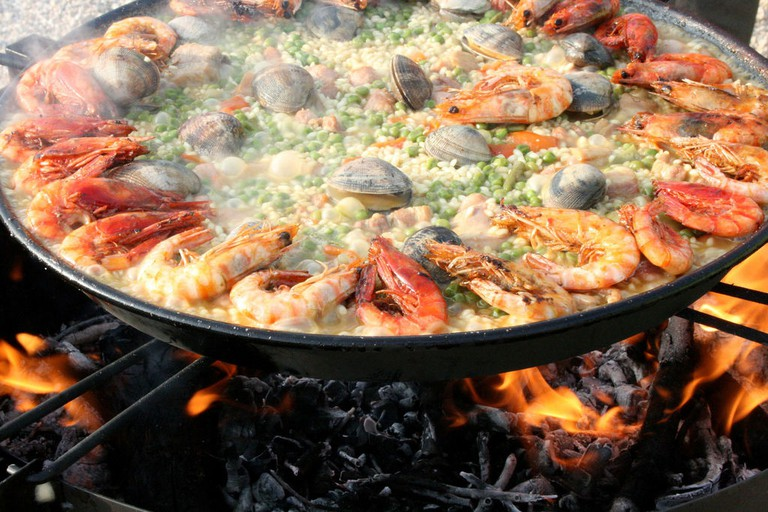 Paella being cooked the traditional way over a wood fire