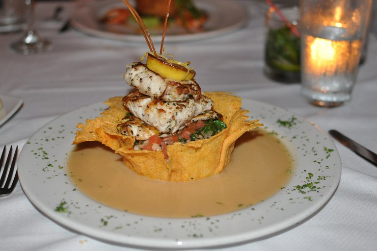 Tigerfish filets on a bed of spaghetti in a bowl made of cheese