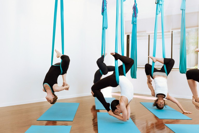 Aerial yoga suspended in hammocks