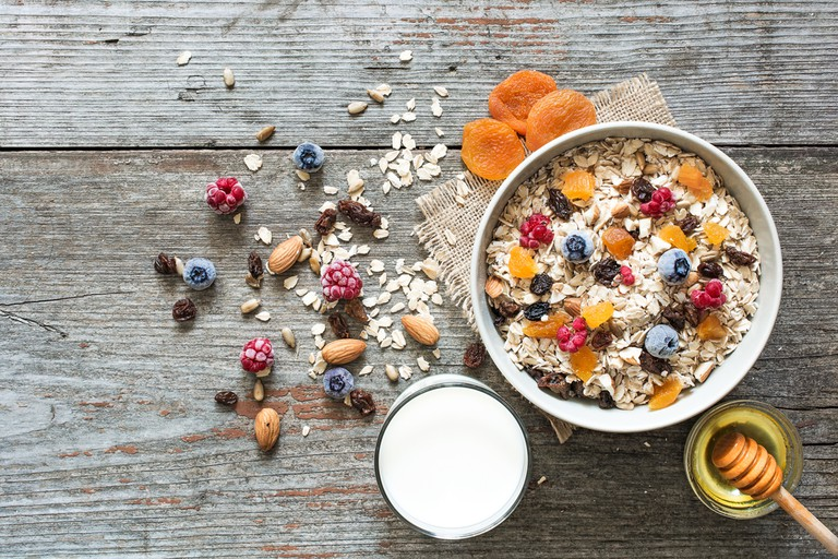 Muesli with nuts, berries, dried fruits, glass of milk and honey
