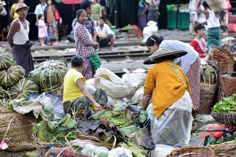 A market overflows with fresh produce near train tracks in Myanmar