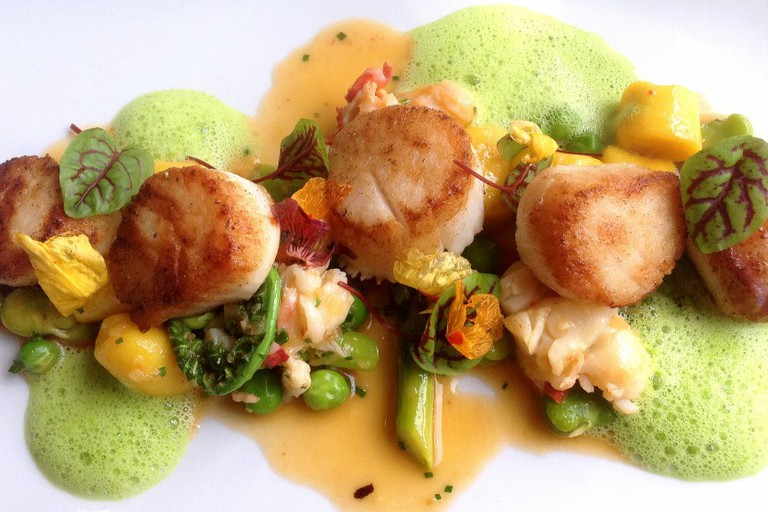 Seared day boat scallops with saffron gnocchi, poached lobster, and early Spring vegetables at Troquet