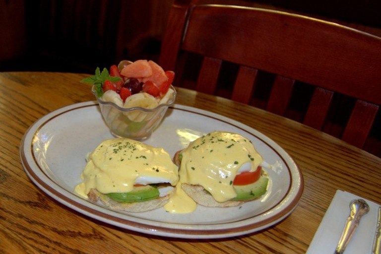 Eggs benedict with a side of fresh fruit