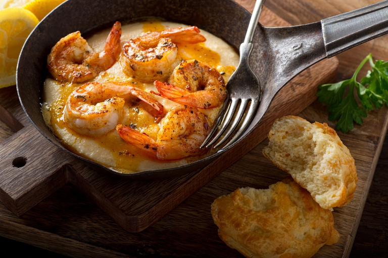 A pan of delicious fresh homemade cajun style shrimp and grits with cheddar biscuit