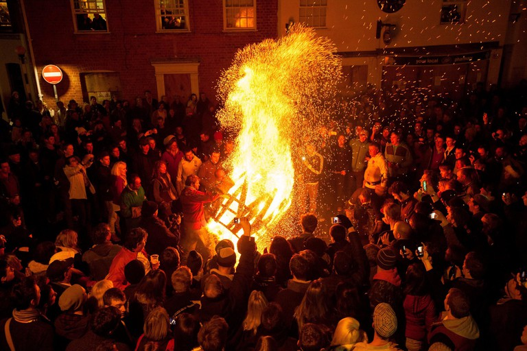Participants run with a burning tar barrel through the streets of Ottery St Mary, Devon.