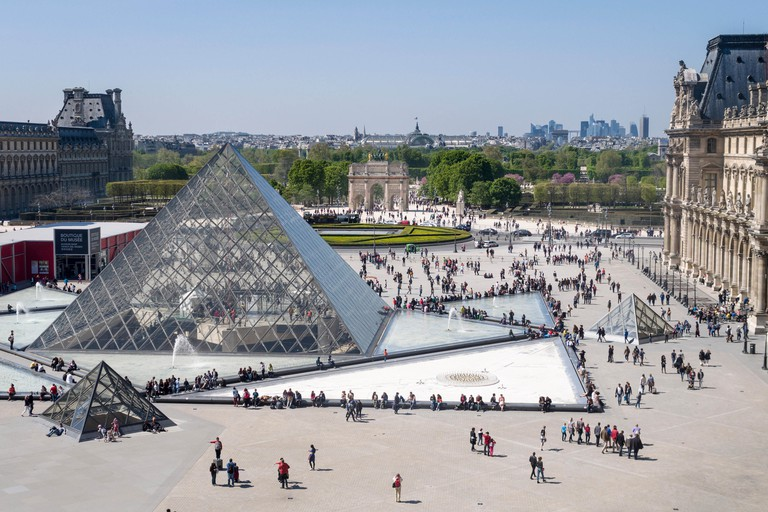 Louvre Pyramid and Paris Beyond. The great glass pyramid in the courtyard of the Louvre Palace with milling tourists & cityscape
