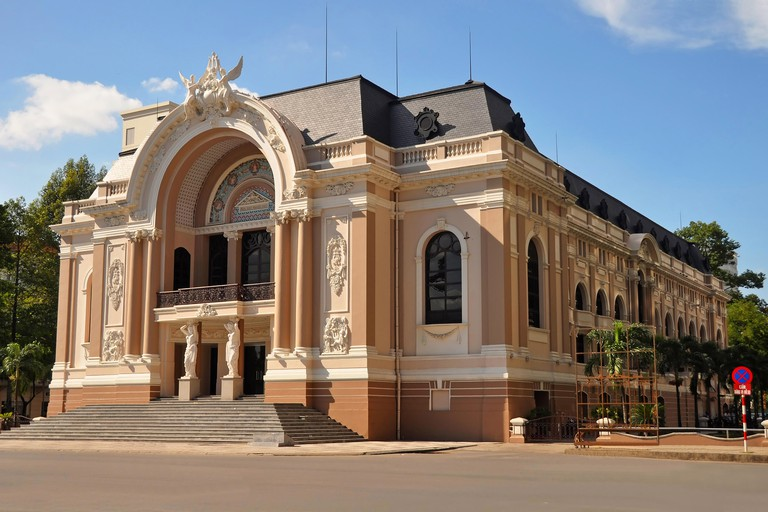 The Saigon Opera House with cyclos on Dong Khoi Street in the foreground. 04 June 2011, Ho Chi Minh City, Vietnam.