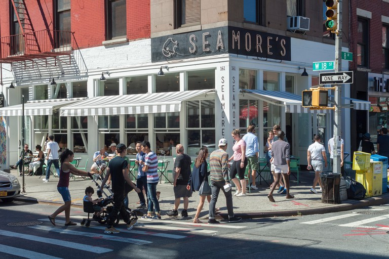 Busy Chelsea neighborhood in New York with Seamore's Restaurant seen on Sunday, July 30, 2017. (© Richard B. Levine)