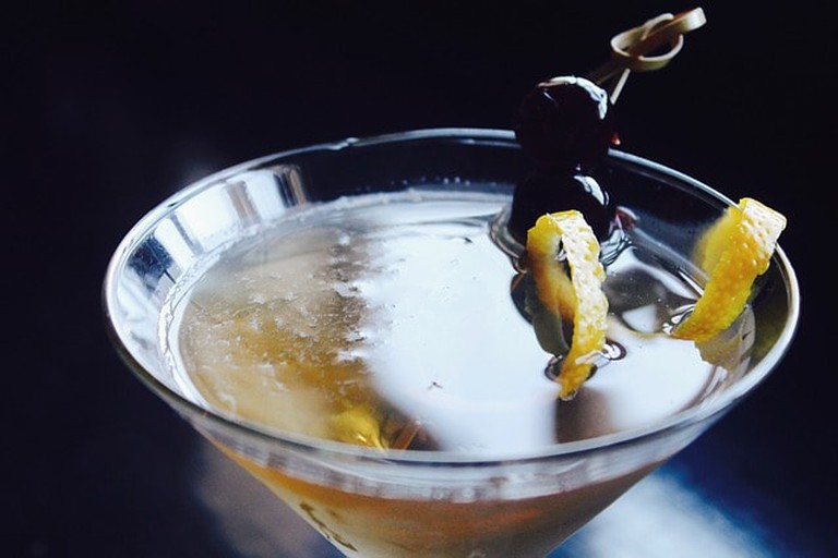 A martini with olive and lemon peel