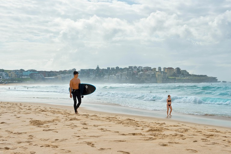 Surfer with board and woman in bikini strolling on Bondi beach