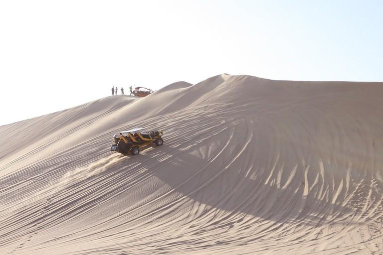 Large dune buggies climbing the dunes