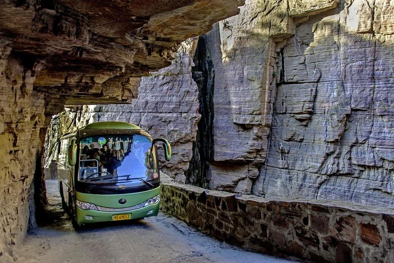 A tourist bus travels along the Guoliang Tunnel through the Wanxian Mountain