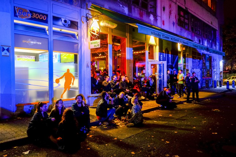 Young people sit at the roadside in front of the bar Mobel Olfe in Berlin.