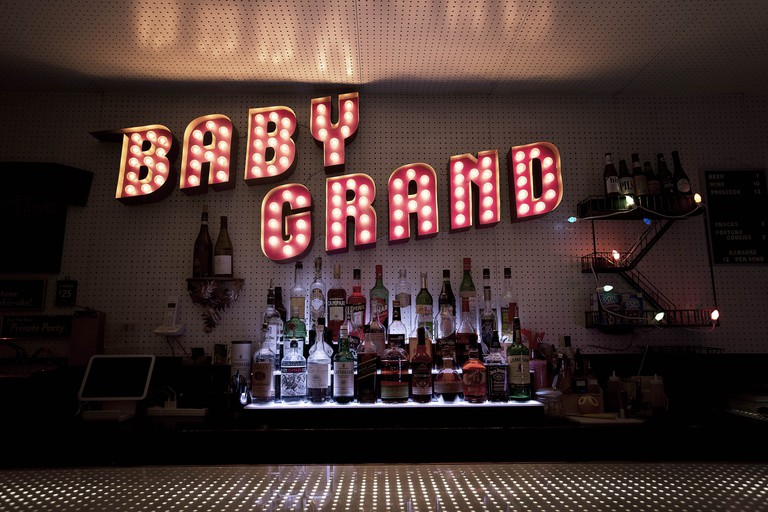 An enormous neon sign hangs above the bar at Baby Grand