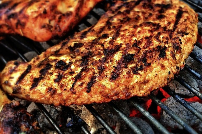 Meat is cooked on a grill at temper