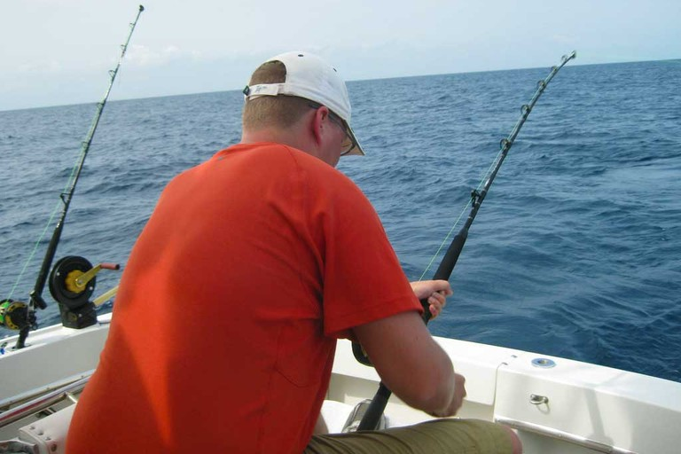 Reeling in a mahi mahi on a fishing charter.