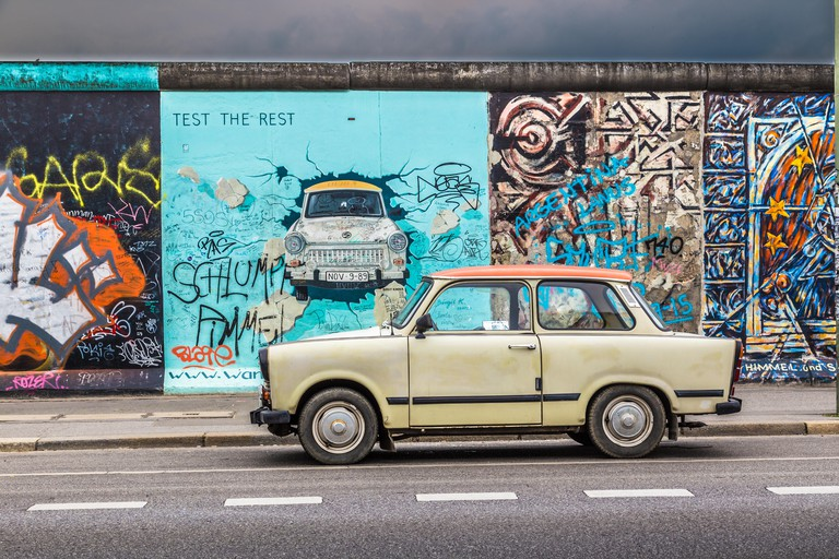 Mural at the East Side Gallery depicting a Trabant Car breaking through the Berlin Wall.