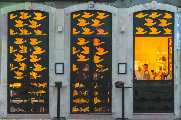 Lisbon, Portugal - 01/03/19: Store front withg metal bird cutouts, Cevicheria. Design black metallic windows and doors in a bird and fish pattern