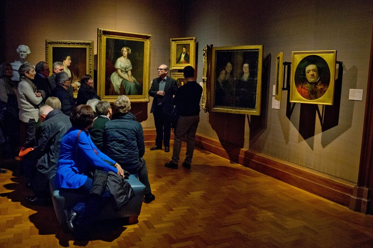 Guide giving a tour to visitors to the Victorian collection at the National Portrait Gallery, London