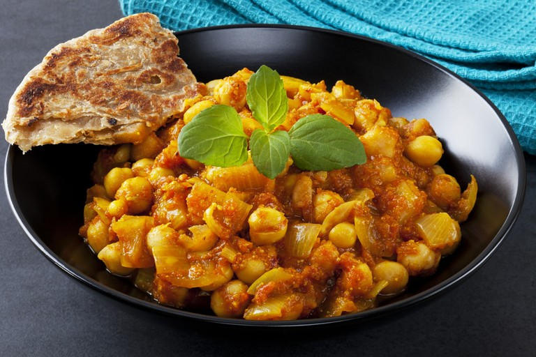 A bowl of hot and sour chickpeas, chana masala, with mint and paratha