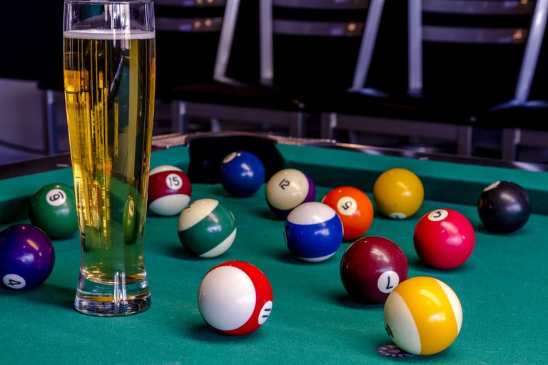 Billiard balls sitting on pool table with glass of beer