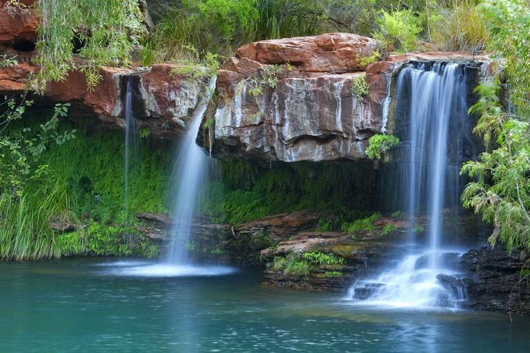 A small waterfall flowing into the Fern Pool in Karijini National Park, Western Australia