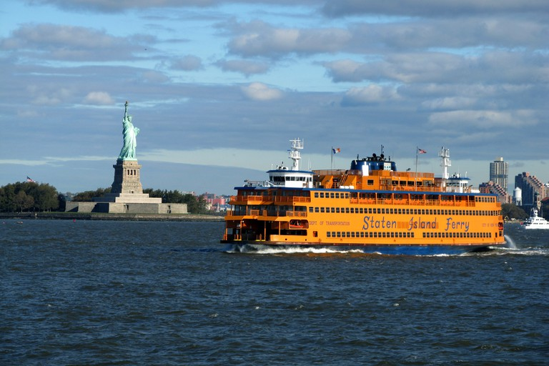 Staten Island Ferry passes the Statue of Liberty on its way from New York to Staten Island, which passengers can ride the ferry for free.