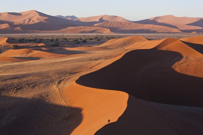 Man climbing sand dunes, Namib Naukluft National Park, Namibia