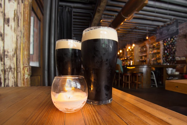 Irish pubs serve dark beer amid candlelight in Queens